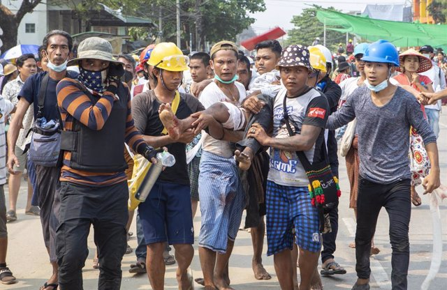 14 March 2021, Myanmar, Yangon: Protesters carry a protester who was shot in his leg by the police with live rounds during a protest against the military coup and the detention of civilian leaders. Five demonstrators have been killed in the latest crackdo