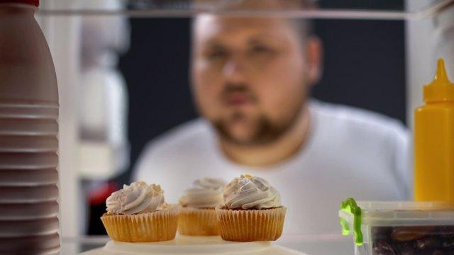 Archivo - Hombre con sobrepeso, hambriento, mirando pasteles de crema edela nevera por la noche.