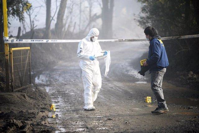Archivo - La Policía forense de Chile tras un ataque incendiario contra un camión en La Araucanía.