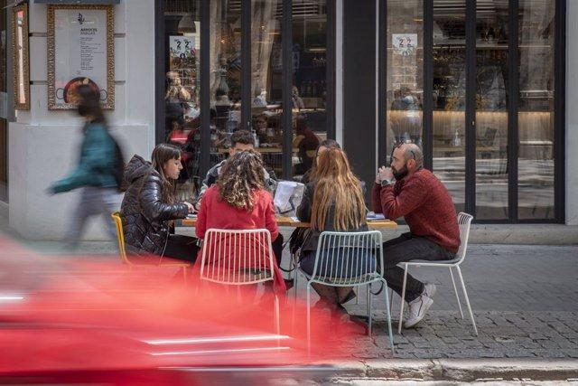 Seis personas sentadas en una terraza el día en que se amplían a seis los comensales por mesa, a 12 de abril de 2021, en Valencia, Comunidad Valenciana (España).