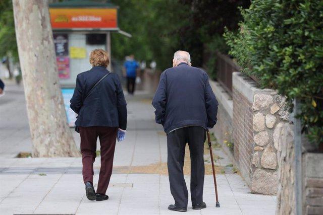 Archivo - Una mujer de edad avanzada pasa al lado de un hombre con bastón.