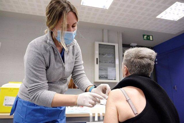 Una sanitària vacuna a una dona a Catalunya, el dia en el qual es reprèn la vacunació amb AstraZeneca.