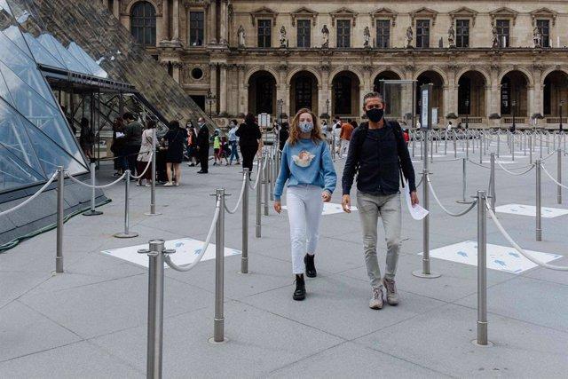 Archivo - Personas con mascarillas junto al Museo del Louvre de París