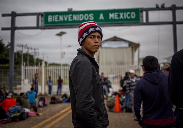 Archivo - Un migrante frente a la frontera de México