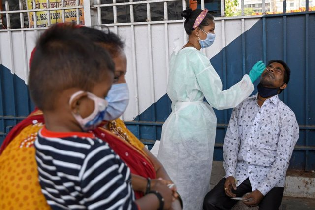 07 April 2021, India, Mumbai: A healthcare worker collects a nasal swab from a man at Dadar railway station. Photo: Ashish Vaishnav/SOPA Images via ZUMA Wire/dpa