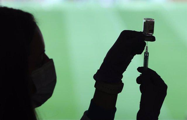 Un profesional sanitaria sostiene una jeringuilla y un vial con la vacuna del Covid-19, en un dispositivo instalado en el Estadio Wanda Metropolitano, en Madrid (España), a 30 de marzo de 2021. La Comunidad de Madrid ha comenzado a vacunar este martes fre