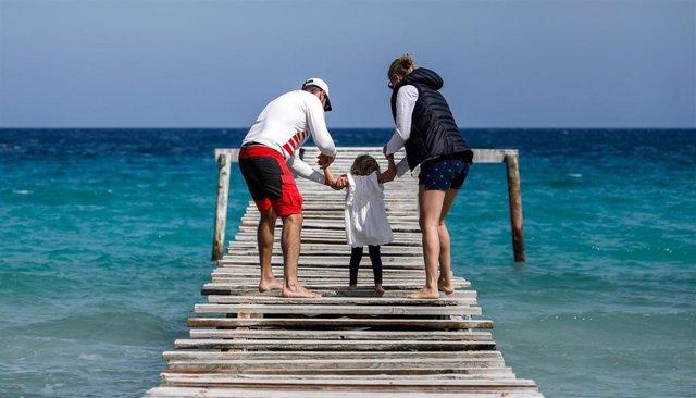 Una familia en una pasarela de madera en playa de Muro.