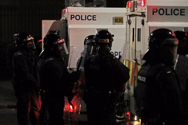 09 April 2021, United Kingdom, Belfast: Anti-riot police stand guard during a violent protest. Violence again flared on the streets of Belfast, with police using water cannons on protesters. Anger on the pro-British side of the community was sparked by th