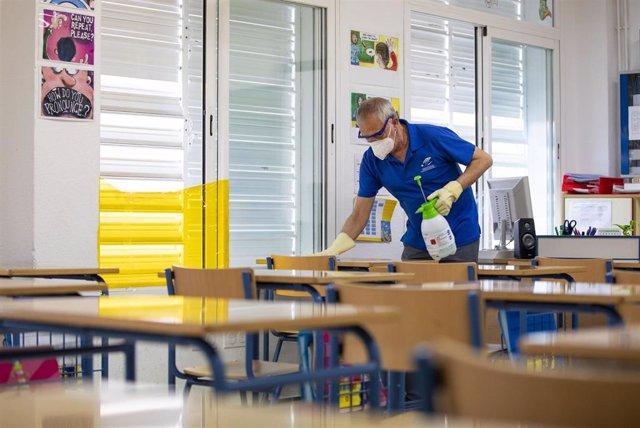 Archivo - Un trabajador limpia las mesas en un colegio andaluz