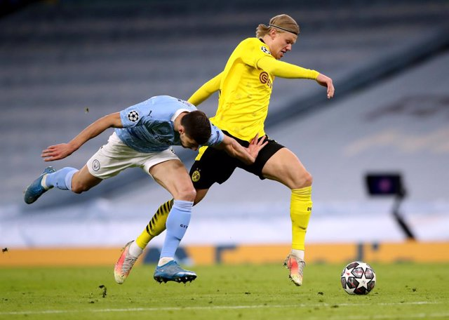 06 April 2021, United Kingdom, Manchester: Manchester City's Ruben Dias (L) and Borussia Dortmund's Erling Haaland (R) battle for the ball during the UEFA Champions League quarter-final first leg soccer match between Manchester City and Borussia Dortmund