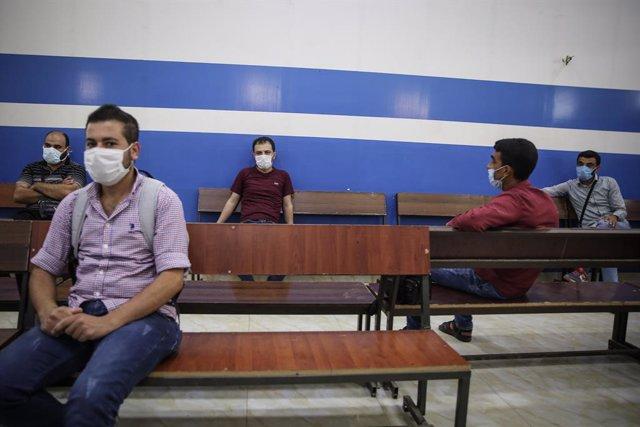 Archivo - Ciudadanos sirios con mascarillas esperando en el paso fronterizo con Turquía en Bab al Hawa