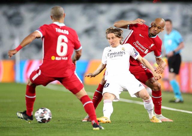 06 April 2021, Spain, Madrid: Real Madrid's Luka Modric battles for the ball with Liverpool's Thiago Alcantara (L) and Fabinho during the UEFA Champions League quarter-final first leg soccer match between Real Madrid and Liverpool at the Alfredo Di Stefan