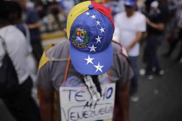 Archivo - Un manifestante con una gorra con la bandera de Venezuela.