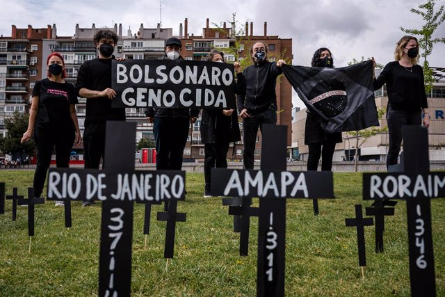 02 April 2021, Spain, Madrid: Group of Brazilian citizens hold Genocidal Bolsonaro banners at the Madrid Rio park during a commemorative act to remember the hundreds of deaths of people from the Coronavirus (Covid-19) pandemic in Brazil. Photo: Diego Rada
