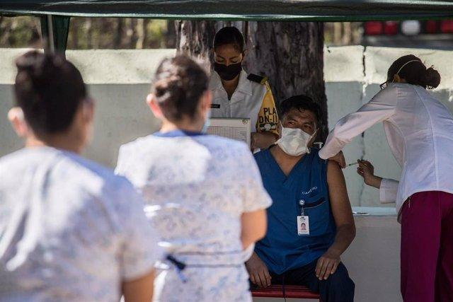 Archivo - Un trabajador sanitario recibe una dosis de la vacuna contra el coronavirus en el Hospital Militar de Ciudad de México.