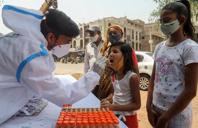 12 April 2021, India, New Delhi: A healthcare worker takes a mouth swab from a child for coronavirus (Covid-19) test at the roadside testing centre at Wazirpur Industrial Area in New Delhi. India overtakes Brazil as the country with the second-largest Cov