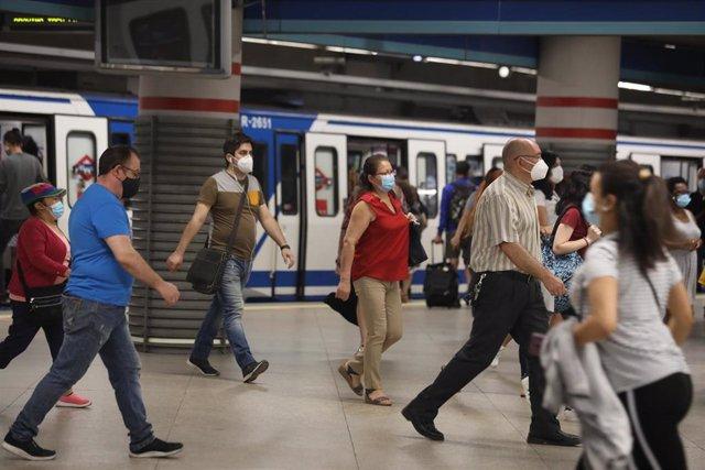 Archivo - Pasajeros con mascarilla salen de un vagón en la estación de Metro de Atocha, en Madrid (España), a 22 de junio de 2020.
