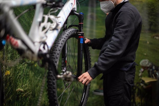 Archivo - Un hombre manipula una bicicleta