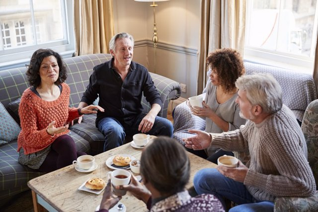 Archivo - 923221396 Group Of Middle Aged Friends Meeting Around Table In Coffee Shop