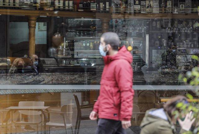 Archivo - Un hombre camina frente a un bar el primer día de la apertura de la hostelería en Valencia
