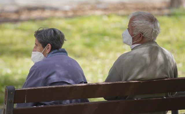 Un hombre y una mujer mayores, sentados en un banco y con mascarilla, en el Parque del Manzanares
