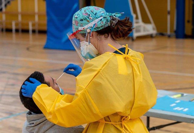 Archivo - Sanitarios trabajando durante las pruebas de cribado de covid-19 con test de antígenos en el pabellón deportivo de 'El Paraguas', en Sevilla, foto de archivo