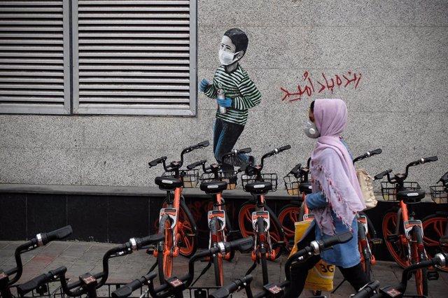 Archivo - Una mujer pasa junto a un mural de un niño con mascarilla en Teherán, Irán