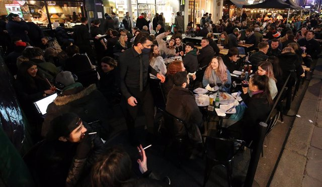 12 April 2021, United Kingdom, London: People crowd at the outdoor areas of pubs in the Soho district, as Corona lockdown restriction eased in London. Photo: Jonathan Brady/PA Wire/dpa