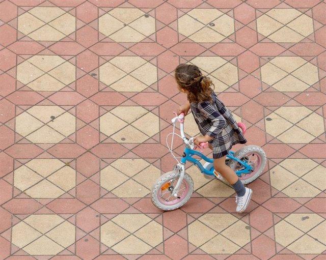 Archivo - Una niña jugando con su bicicleta en la Plaza de España del Parque de Maria Luisa, en Sevilla.