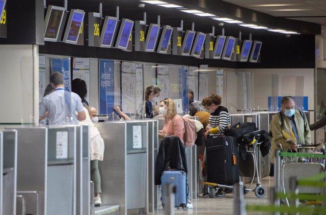 Varias personas frente a un mostrador de Aerolíneas Argentinas, en la Terminal T1 del Aeropuerto Madrid - Barajas Adolfo Suárez, en Madrid (España), a 30 de marzo de 2021. Aerolíneas Argentinas ha cancelado varios de sus vuelos internacionales para reduci