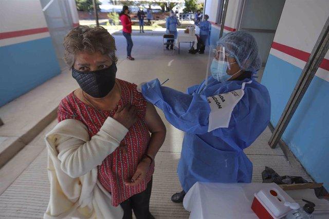 Archivo - Un mujer recibe una dosis de la vacuna contra la COVID-19 en Etzatan, México.