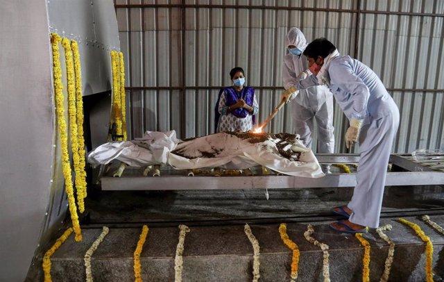 Familiares de una persona fallecida por coronavirus realizan rituales antes de la cremación.