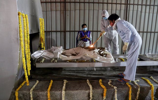 13 April 2021, India, New Delhi: Relatives of a person died of COVID-19 diseas, perform rituals on his bodz before the cremation in a CNG furnace at Nigambodh Ghat crematorium in New Delhi. Photo: Naveen Sharma/SOPA Images via ZUMA Wire/dpa