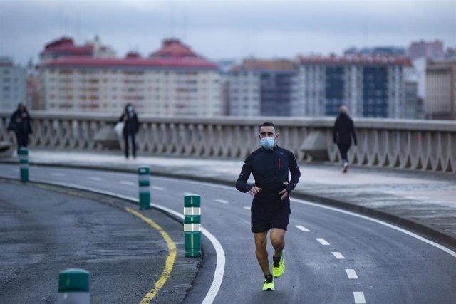 Archivo - Una persona corre en solitario y con mascarilla un día después de la entrada en vigor de la normativa que obliga a los deportistas a hacer deporte al aire libre con mascarilla y sin compañía en Galicia, en A Coruña, Galicia, (España), a 27 de en