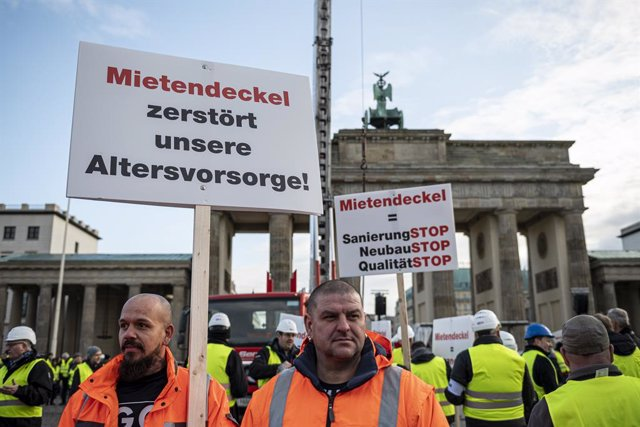 Archivo - 09 December 2019, Berlin: People hold placards in front of the Brandenburg Gate during a rally organized by an alliance of the Berlin construction and housing industry and landlords against rent caps, proposed by the state of Berlin to set an up