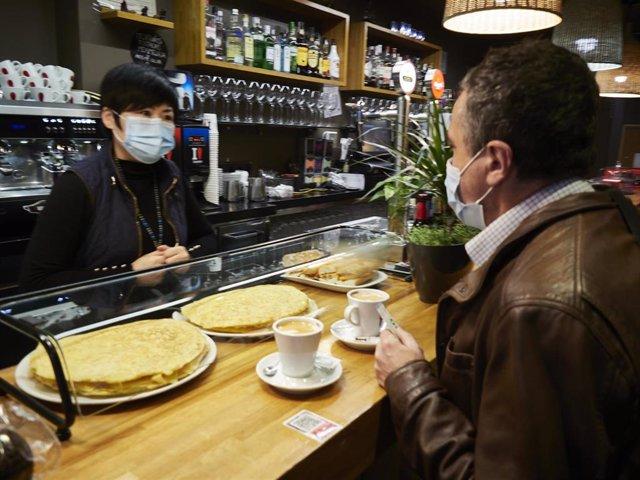 Archivo - Una camarera y un cliente en el interior de un bar.