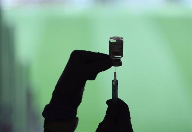 Un profesional sanitaria sostiene una jeringuilla y un vial con la vacuna del Covid-19, en un dispositivo instalado en el Estadio Wanda Metropolitano, en Madrid (España), a 30 de marzo de 2021.