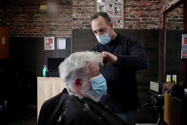 Un hombre se corta el pelo en una barbería lisboeta aprovechan la reapertura de negocios prevista en el plan de desescalada del Gobierno.