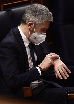 El ministro del Interior, Fernando Grande-Marlaska, observa su reloj en una sesión plenaria en el Congreso