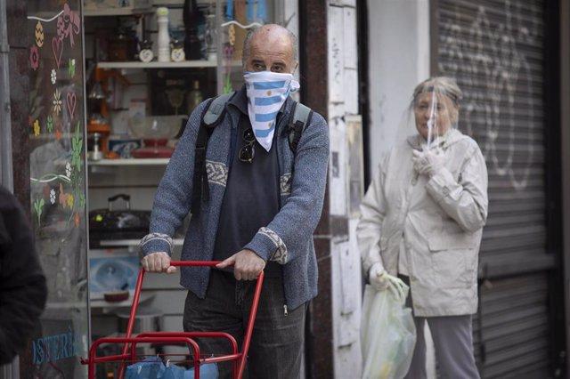 Archivo - Personas con mascarilla y otras protecciones contra el coronavirus en Argentina