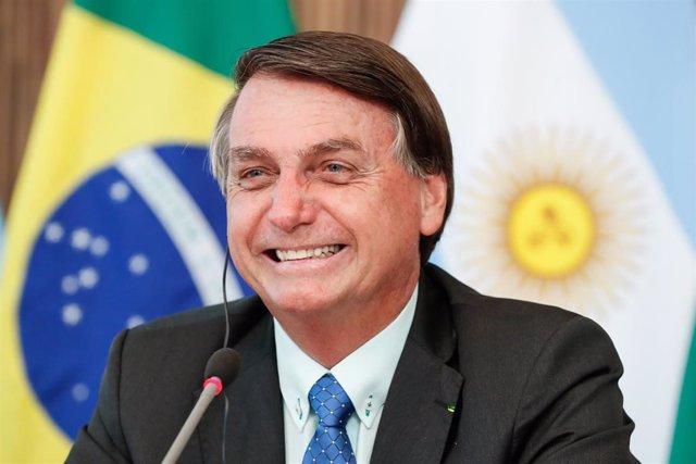 Archivo - El presidente brasileño, Jair Bolsonaro, delante de las banderas de Brasil y Argentina.