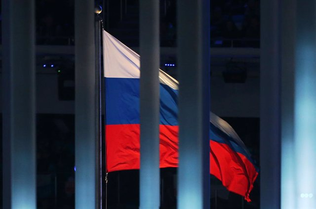 Archivo - FILED - 07 March 2014, Russia, Sochi: The Russian flag is pictured behind a fence during the Opening ceremony of the 2014 Winter Paralympics at the Fisht Olympic stadium in Sochi.  Russia is facing a four-year sporting ban  in connection with th