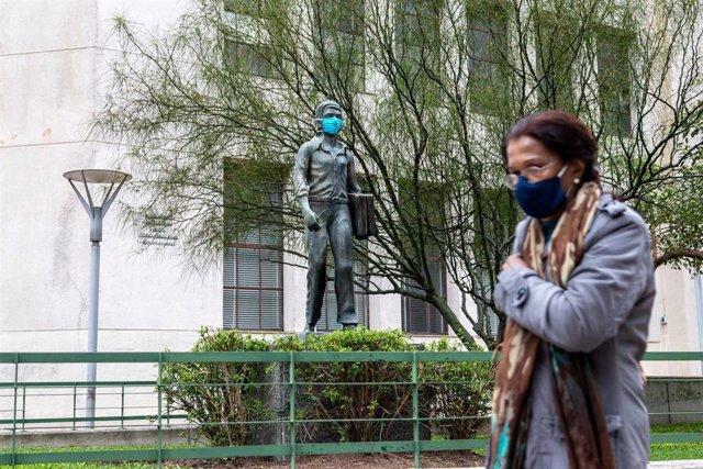 Archivo - Una mujer pasa frente a una estatua con mascarilla en Montevideo, acción promovida por el Gobierno para fomentar el uso de mascarilla.