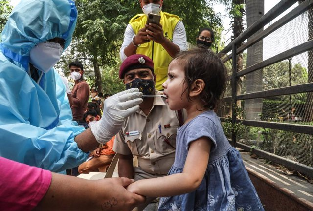 15 April 2021, India, New Delhi: A healthcare worker in protective suit collects a mouth swab sample from a kid for a COVID-19 RT-PCR test outside the DT City Centre Mall. Photo: Naveen Sharma/SOPA Images via ZUMA Wire/dpa