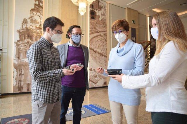 Imágenes de investigadores del proyecto mostrando algunos de los dispositivos que se van a utilizar en el hotel Alfonso XIII, donde se realizarán pruebas piloto, y de las reuniones mantenidas con empresarios turísticos