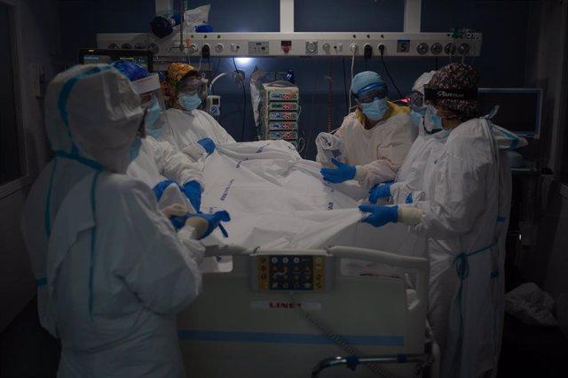 Archivo - Arxiu - Treballadors sanitaris atenen un pacient en una unitat de vigilància intensiva.