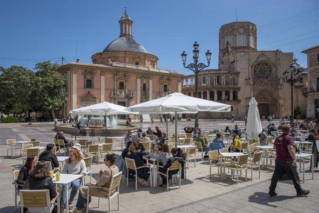 Varias personas en la terraza de un bar, el día en que se amplían a seis los comensales por mesa, a 12 de abril de 2021, en Valencia, Comunidad Valenciana (España). A partir de hoy, seis personas podrán sentarse juntas en bares y terrazas. También se flex