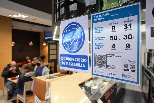 Archivo - Varios carteles donde se muestra el aforo y el código QR en la puerta de un restaurante en A Coruña, Galicia (España), a 12 de marzo de 2021. Este viernes entra en vigor la obligatoriedad de que los establecimientos tengan en un lugar visible un
