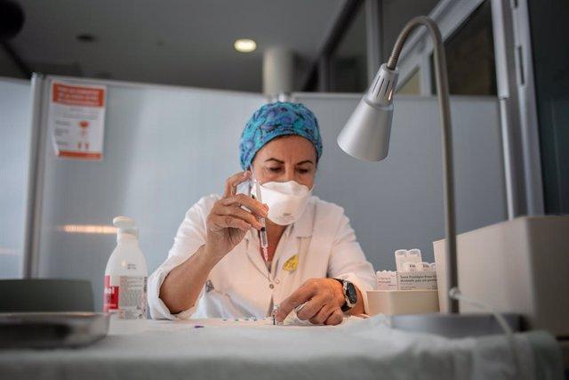 Archivo - Arxivo - Una infermera prepara la vacuna Pfizer-BioNtech contra el COVID-19 abans d'administrar-la-hi a un professional sanitari a l'Hospital de la Santa Creu i Sant Pau de Barcelona.