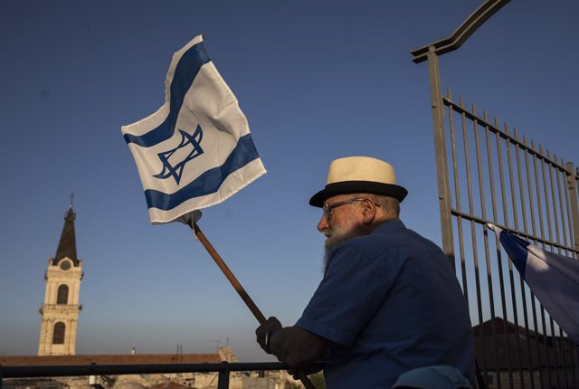 Archivo - 21 May 2020, Israel, Jerusalem: A man holds the Israeli national flag as he takes part in the annual flag parade to mark Jerusalem day celebrations. Jerusalem Day is an Israeli holiday that commemorates the establishment of Israeli control over